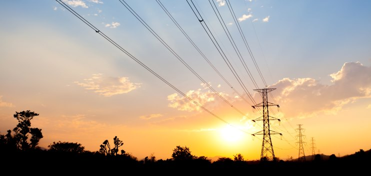 Electricity pylons silhouetted against sunset